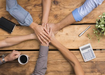 Closeup of business colleagues with their hands stacked. Business team showing unity with their hands together. Close up of business partners making pile of hands at meeting. Concept of united business team work.
